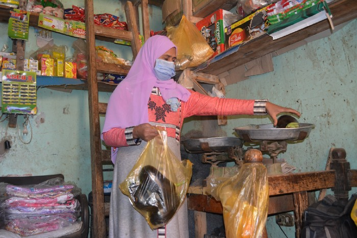 Identifying the local need for groceries in her small village in Assiut, Radia now uses the additional profit to support a cloth making side business.